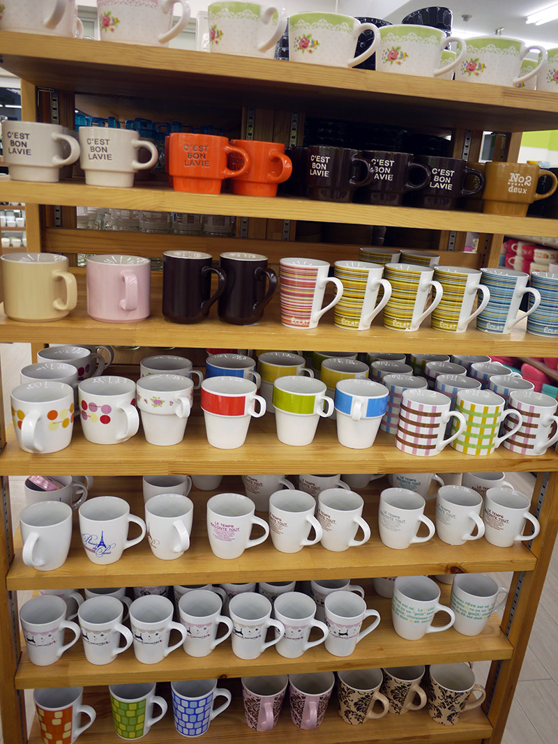 Colorful mugs in solid colors and prints on a shelf