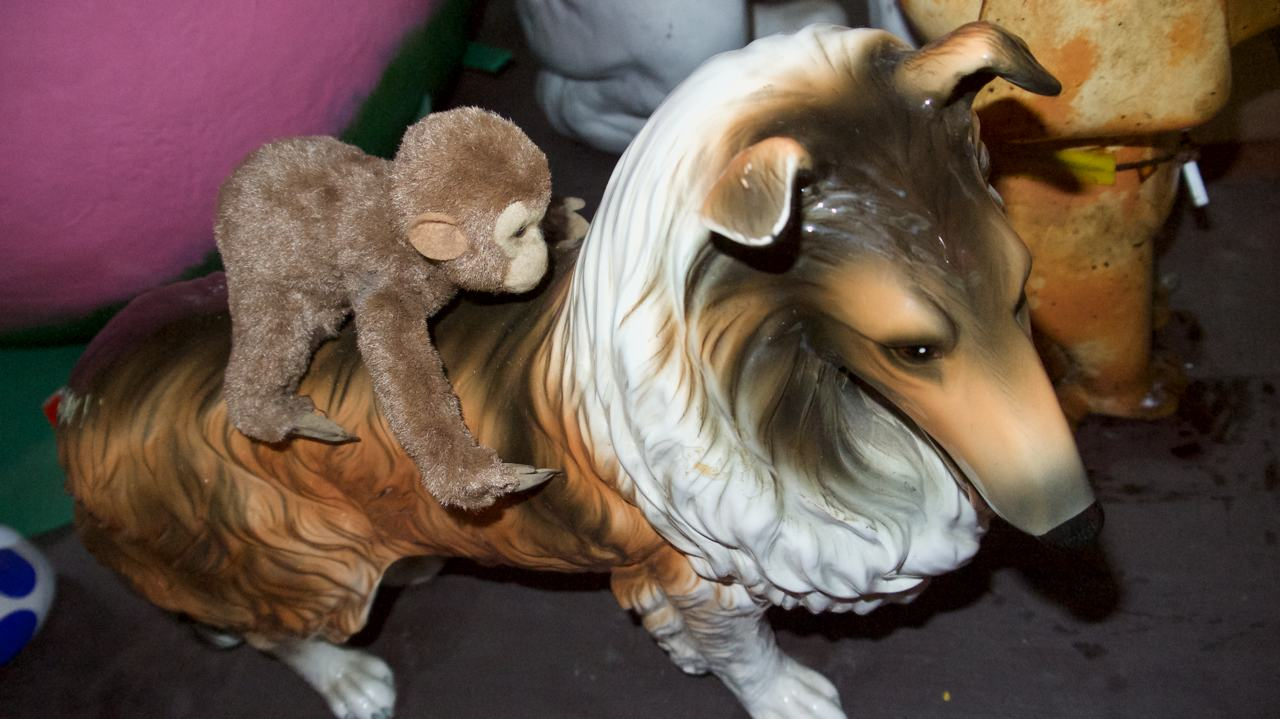 collie statue with monkey plush