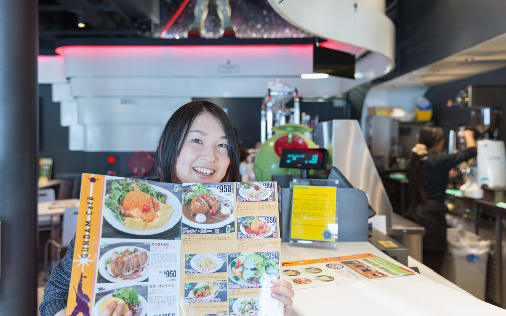 woman holding up menu from gundam cafe akihabara