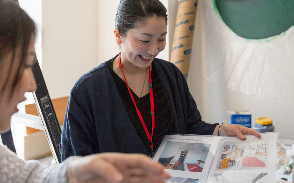 japanese artist holding a book of her work
