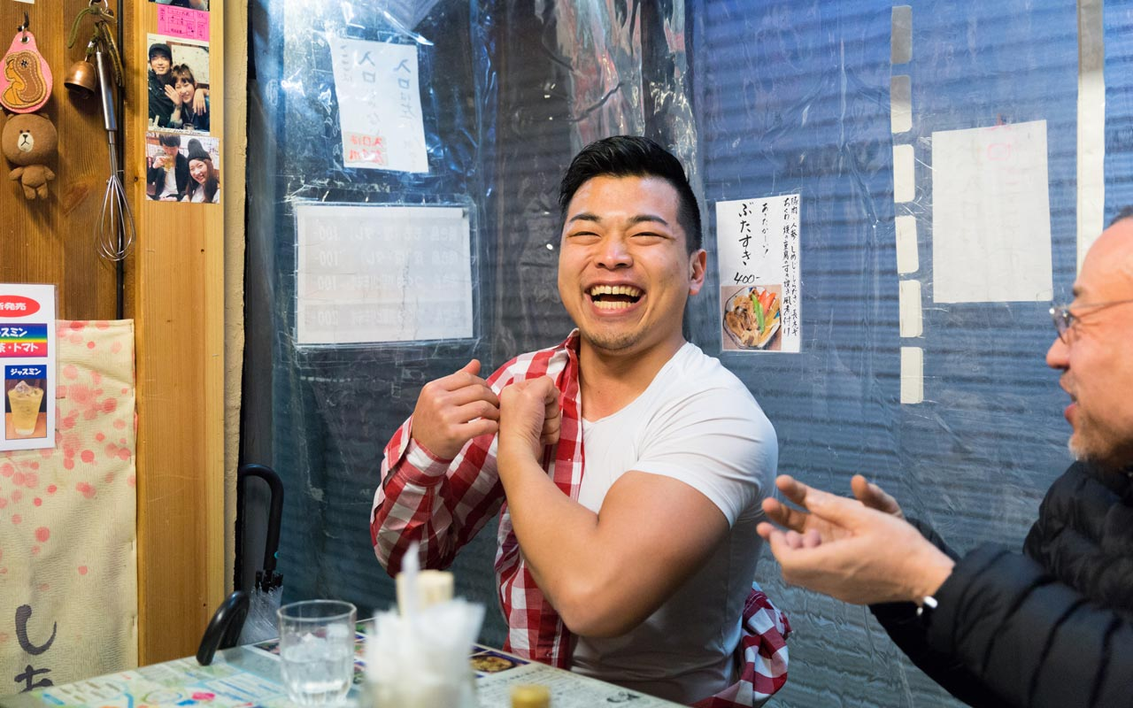 japanese man laughing in harmonica yokocho bar