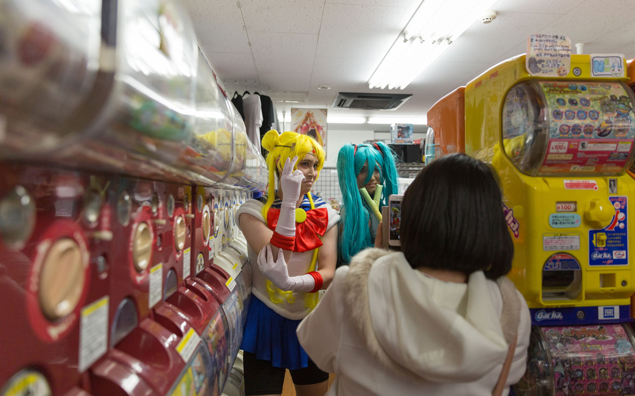two men cosplaying by a row of gachapon machines