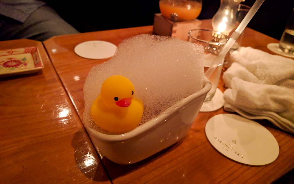 alcoholic beverage inside a small bathtub with rubber duck