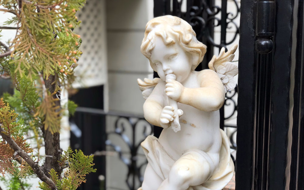 statue of a cherub playing flute
