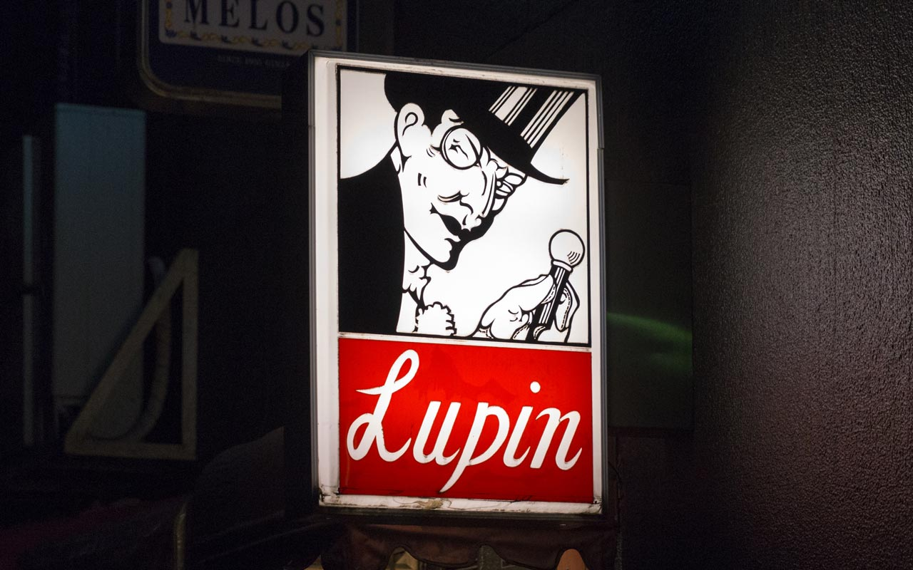 red and white sign for a bar called lupin