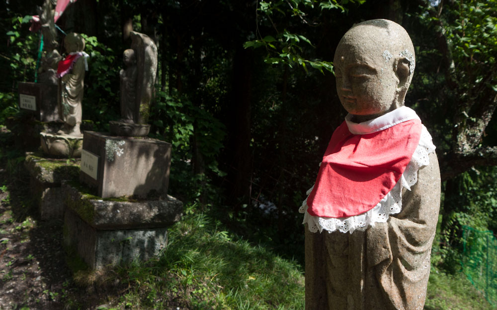 three jizo statues wearing red bibs
