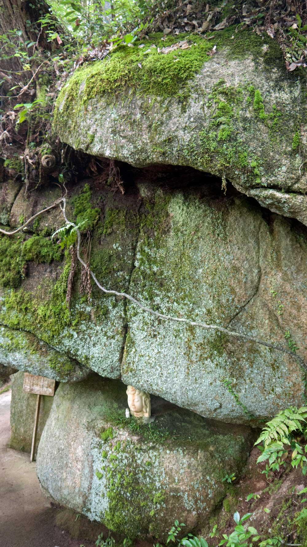 statue head wedged between two boulders