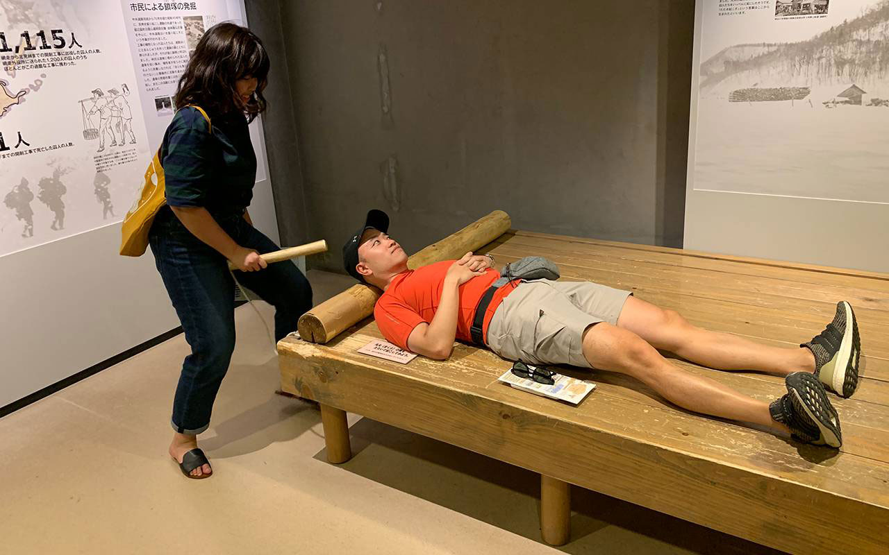 Museum visitor experiencing being woken up by someone banging on the wooden pillow